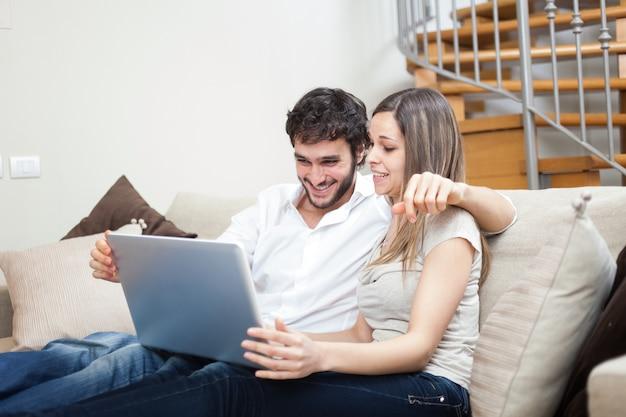 Couple utilisant un cahier tout en se relaxant sur le canapé