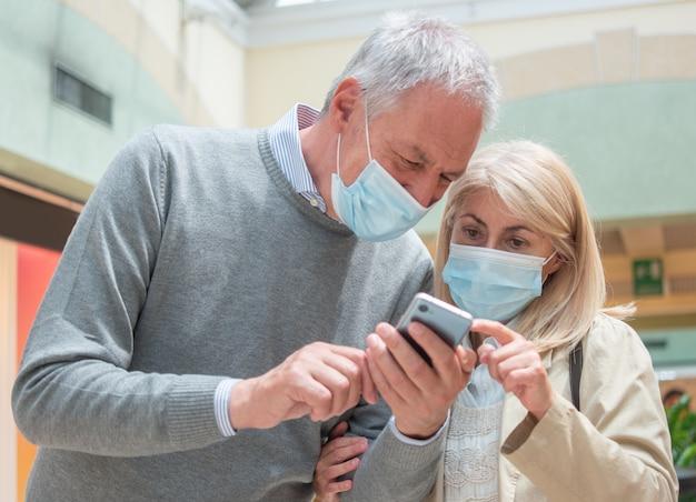 Couple utilisant leur smartphone ensemble pendant la pandémie de coronavirus