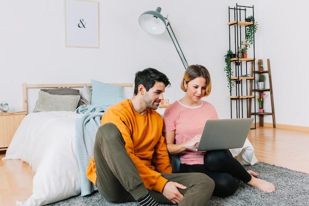 Couple utilisant un ordinateur portable dans la chambre