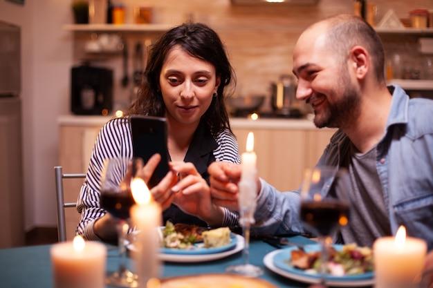 Couple utilisant un téléphone pendant un dîner romantique dans la cuisine et des bougies allumées sur la table. des adultes assis à table dans la cuisine naviguant, cherchant, utilisant des smartphones, internet, célébrant un anniversaire.