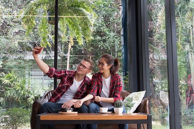 Couple utilise un téléphone intelligent pour prendre une photo de selfie. homme caucasien et femme asiatique s'asseoir sur le canapé.