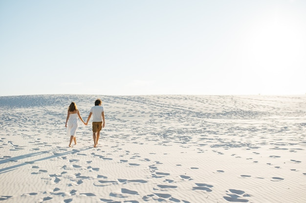 Couple de vacances marchant sur la plage ensemble amoureux se tenant autour de l'autre. heureux jeune couple interracial.