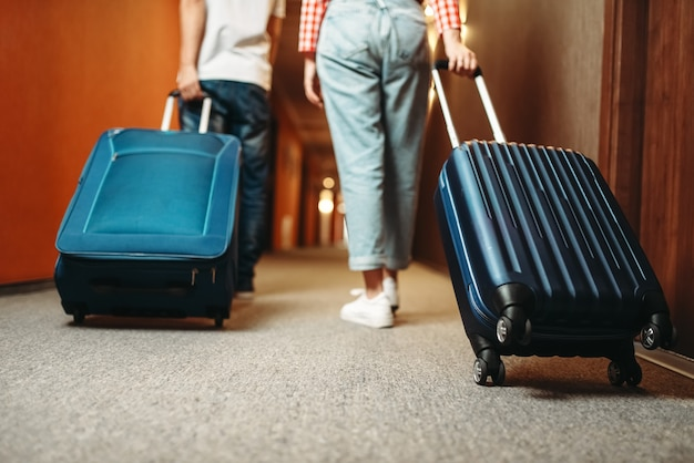 Couple avec valise en marchant dans le couloir de l'hôtel