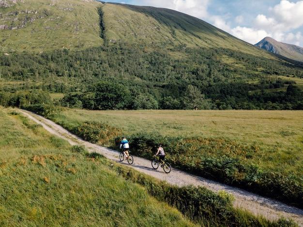Couple à vélo sur une route dans les highlands écossais