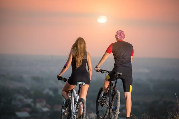 Couple avec des vélos de sport au coucher du soleil
