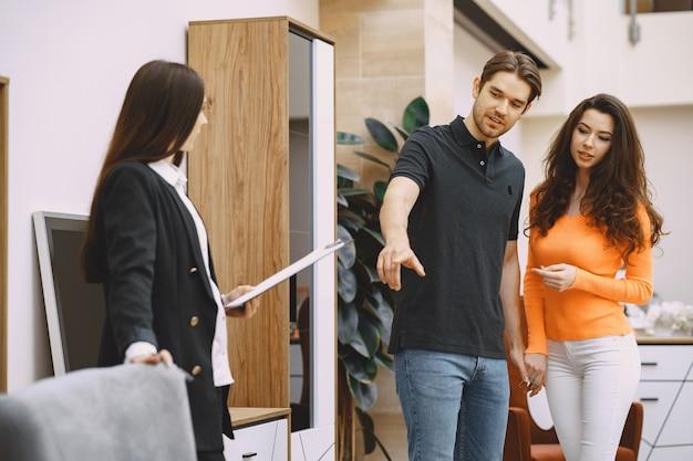 Couple avec vendeur en magasin de meubles