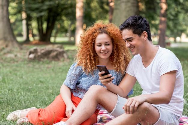 Couple, vérification, téléphone portable, dans parc, s'amuser