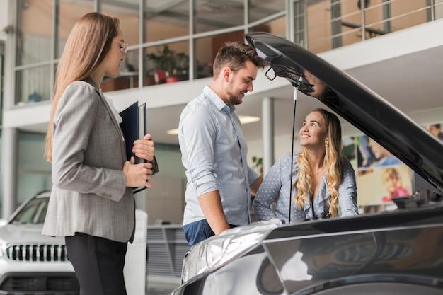 Couple, vérification, voiture, moteur, salle exposition