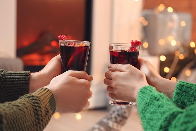 Couple avec verres de délicieux vin chaud près de la cheminée