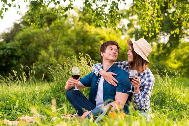 Couple avec verres à vin étreignant dans la nature