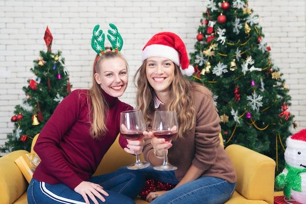 Couple avec des verres de vin rouge près de la cheminée. belle jeune femme caucasienne en pull et avec bonnet de noel sur la tête assis sur le canapé à côté de l'arbre de noël