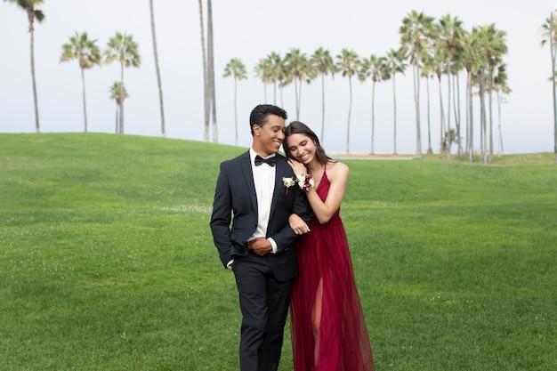 Couple en vêtements de bal de fin d'études à l'extérieur