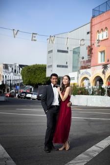 Couple en vêtements de bal de fin d'études posant ensemble