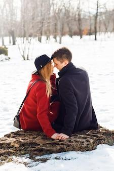 Couple en vêtements d'hiver s'embrasser un jour de neige