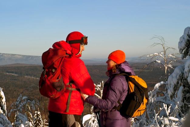 Un couple en vêtements d'hiver avec des sacs à dos se regarde debout au sommet de la montagne