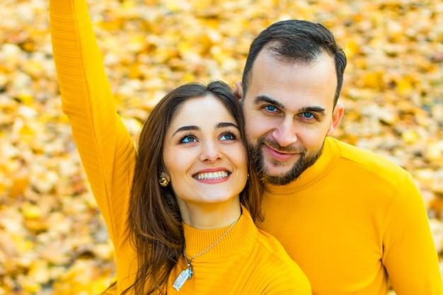Couple vêtu de cols roulés jaunes étreignant sur un fond de feuilles d'automne