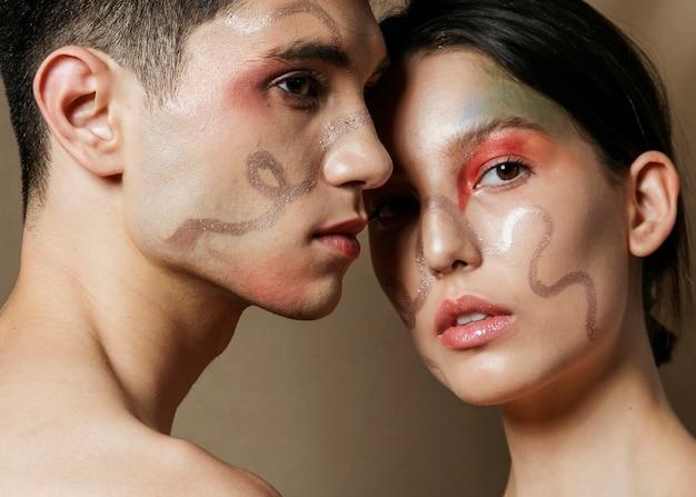 Couple avec des visages peints posant séduisante