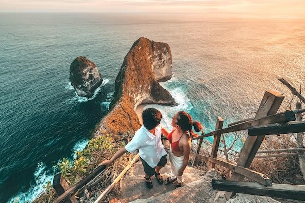 Couple voyage vue du paysage avec la plage de kelingking, île de nusa penida à bali, indonésie