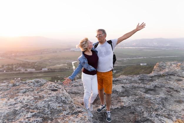 Couple voyageant plein coup debout sur la falaise