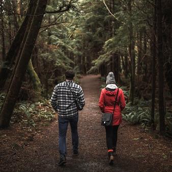 Couple voyageant à travers la forêt