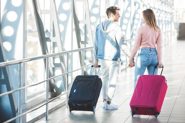 Couple voyageant. voyage amoureux. jeune homme et femme à l'aéroport. visite en famille.