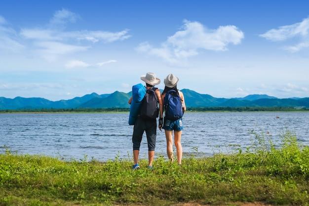 Couple voyageur debout près du lac dans la montagne