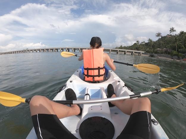 Couple voyageur kayak ensemble sur la mer à partir de la vue arrière.