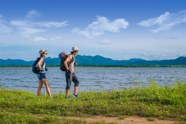Couple voyageur marchant près du lac dans la montagne