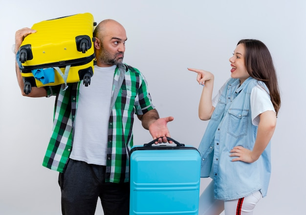 Couple de voyageurs adultes homme malheureux tenant des valises l'un d'eux sur l'épaule femme joyeuse en gardant la main sur la taille et en le pointant à la fois en se regardant