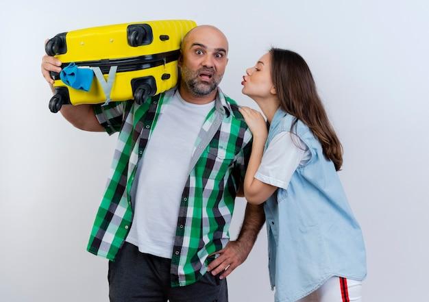 Couple de voyageurs adultes impressionné homme tenant valise sur l'épaule à la main sur la taille femme touchant son épaule en le regardant et faisant le geste de baiser