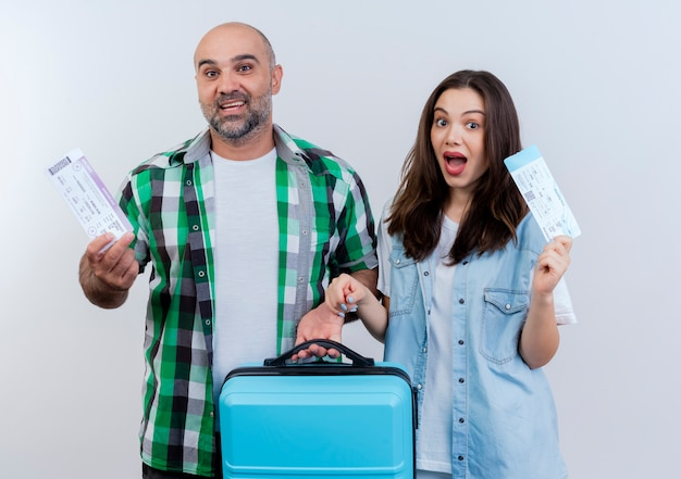 Couple de voyageurs adultes impressionnés man holding valise à la fois tenant un billet de voyage à la recherche