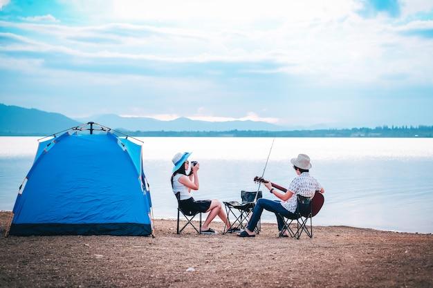 Couple de voyageurs font du camping et pêchent au bord du lac en vacances.