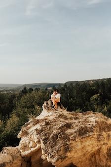 Couple de voyageurs homme et femme assis sur des pierres, étreignent et se détendent.