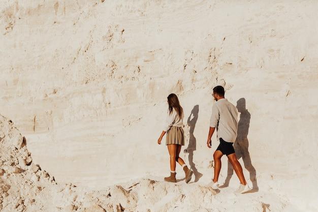 Couple de voyageurs marchant le long de la montagne rocheuse près de la falaise blanche