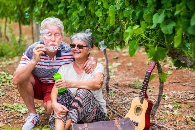 Couple de voyageurs matures alternatifs soufflant des bulles de savon dans un vignoble