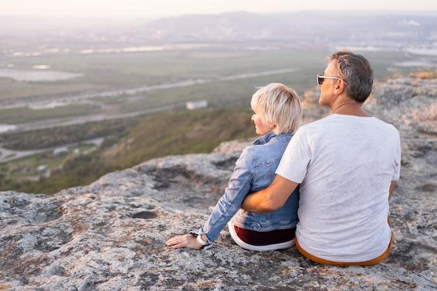 Couple de voyageurs plein coup assis sur la falaise