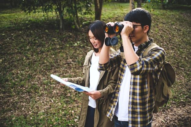 Couple de voyageurs en randonnée en montagne avec carte d'itinéraire et navigateur.