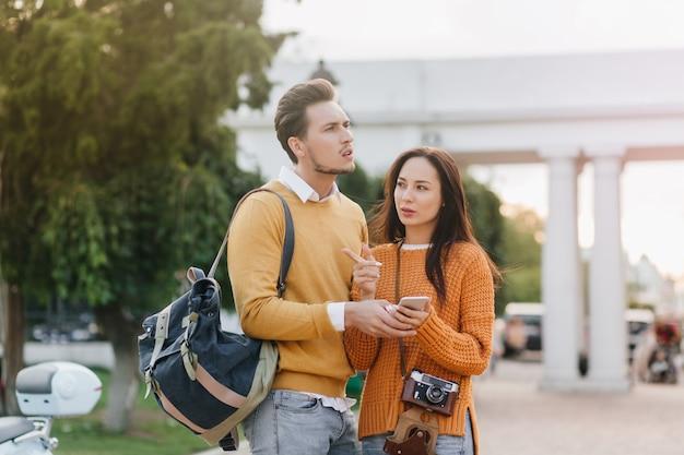 Couple de voyageurs regardant autour avec des expressions de visage inquiet