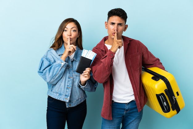 Couple de voyageurs tenant une valise sur bleu montrant un signe de silence geste mettant le doigt dans la bouche