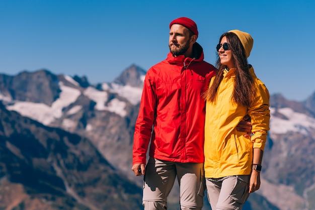 Un couple de voyageurs en tenue de randonnée sur fond de montagnes. deux touristes au sommet de la montagne. un homme et une femme dans les montagnes. deux voyageurs en vestes colorées, gros plan.