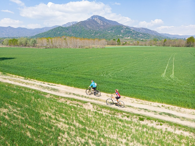 Couple de vue aérienne s'amusant à faire du vélo de montagne sur un chemin de terre en journée ensoleillée,