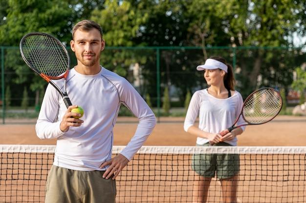 Couple vue de face sur un court de tennis