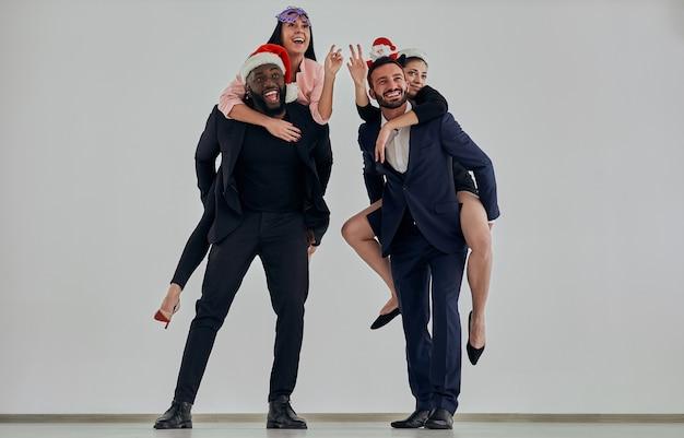 Les couples d'affaires en geste de chapeau rouge sur fond de mur blanc