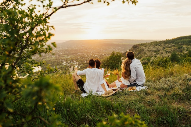 Couples aimants buvant du vin en été sur la montagne au coucher du soleil.