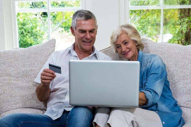 Couples aînés, achats, ligne, portable utilisation, à, salon
