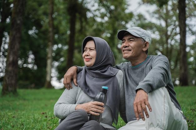 Couples aînés, à, a, bouteille eau, séance, dans jardin