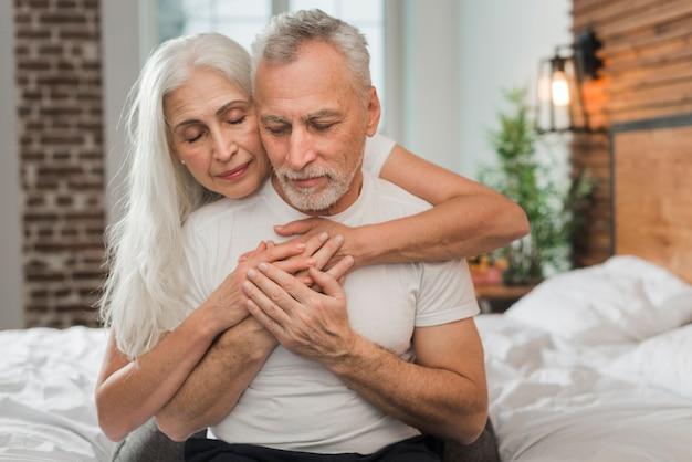 Couples aînés, dans lit, étreindre