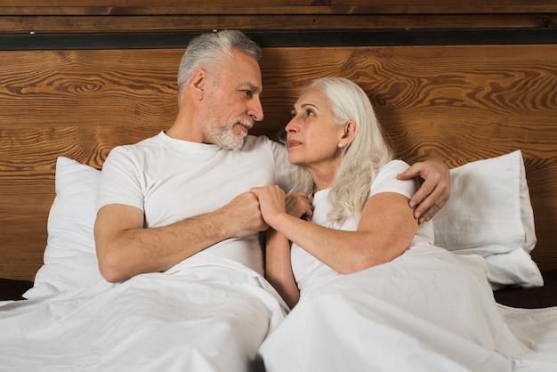 Couples aînés, dans lit, tenant mains
