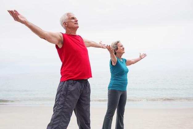 Couples aînés, debout, à, bras étendus