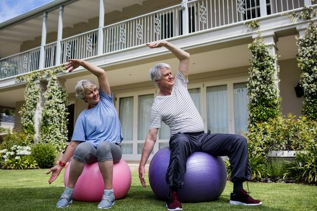Couples aînés, exécuter, étirage, exercice, sur, boule fitness